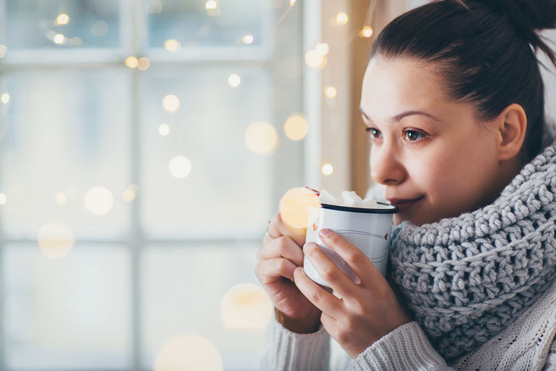 woman drinking hot chocolate in a cozy sweater